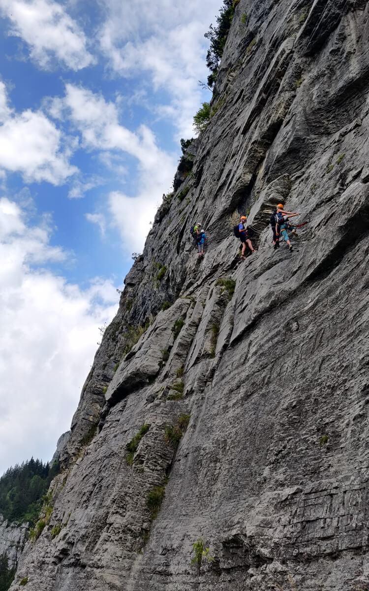 Un groupe sur la paroi rocheuse. la via ferrata curalla est aérienne!